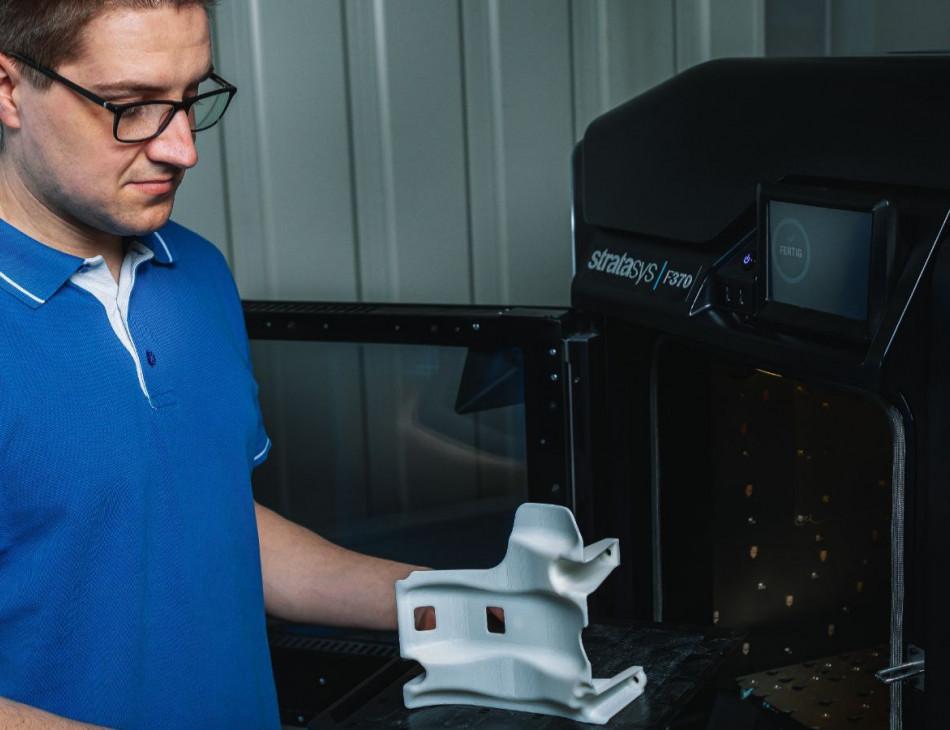 MItarbeiter holt ein fertiges Produkt aus dem 3D-Drucker